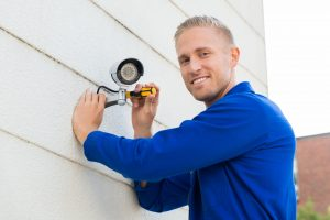 48038725 - smiling young technician installing camera on wall with screwdriver